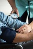 Oudste die bloeddruk hebben gemeten Stock Fotografie
