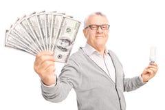 Oudste die een energie efficiënt gloeilamp en een geld houden Royalty-vrije Stock Afbeelding