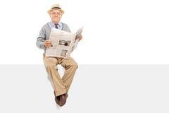 Oudste die een krant houdt op een paneel gezet Stock Afbeelding