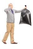 Oudste die een stinky vuilniszak dragen Stock Foto
