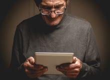 Oudste die een tablet in handen houden royalty-vrije stock fotografie