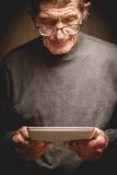 Oudste die een tablet in handen houden Stock Afbeelding