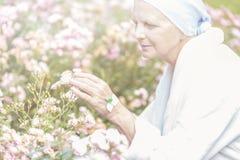 Oudste die met kanker van bloemen in een tuin genieten royalty-vrije stock foto