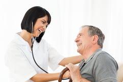 Oudste die met zijn verpleegster lacht Stock Foto's