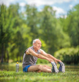 Oudste die uitrekkende oefeningen in park doen Stock Foto's