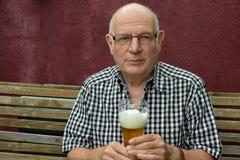 Oudste die van een bier genieten stock afbeelding