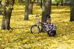 Oudste en zijn fiets in de herfstpark Royalty-vrije Stock Afbeeldingen