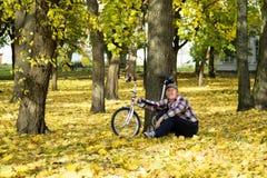 Oudste en zijn fiets in de herfstpark Stock Afbeelding