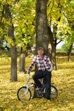 Oudste en zijn fiets in de herfstpark Stock Foto's