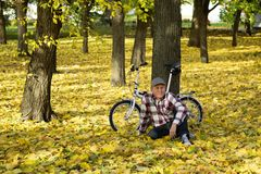 Oudste en zijn fiets in de herfstpark Stock Fotografie