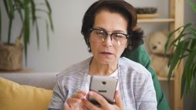 Oudste geconcentreerde vrouw die in glazen bericht schrijven stock videobeelden