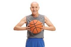 Oudste met een basketbal die de camera en het glimlachen bekijken Royalty-vrije Stock Fotografie