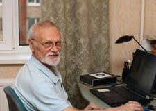 Oudste met laptop Stock Foto's