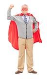 Oudste in superherouitrusting met zijn vuist in de lucht Stock Afbeeldingen