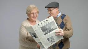 Oudsten die een krant en het glimlachen lezen stock footage