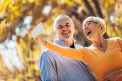 Oudsten die selfies van hen nemen die pret buiten in het de herfstbos hebben stock afbeeldingen