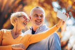 Oudsten die selfies van hen nemen die pret buiten in het de herfstbos hebben stock foto's
