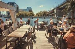 Oudsten en jongeren die diner hebben bij rivierrestaurant dichtbij de grote concrete brug Stock Fotografie