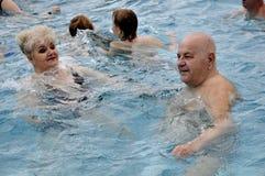 Oudsten in het simming van pool Stock Foto