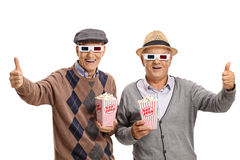 Oudsten met 3D glazen en popcorn die hun duimen tegenhouden Royalty-vrije Stock Foto