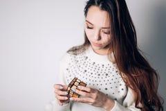 OUFA, RUSSIE - 14 JANVIER 2018 : Une belle femme de brune dans un chandail blanc rassemble un puzzle, le cube d'un Rubik d'or de  photo libre de droits