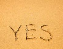 OUI - écrit en sable sur la texture de plage d'océan Images libres de droits