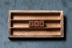 Oui et concept d'accord La boîte de vintage, les cubes en bois avec des lettres de style ancien sur la pierre grise a donné au fo photographie stock