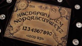 Ouija单独移动并且说不 皇族释放例证