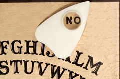Ouija board with the planchette pointing to NO Stock Image