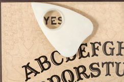 Ouija board with the planchette pointing to YES Stock Image