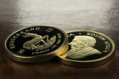 1 ounce gold bullion coins. South African 1 ounce gold bullion coins on wooden Background Royalty Free Stock Photography