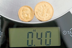 0.4 ounces of pure gold. Russian old gold coins 5 and 10 rubles of pure gold on the scales Royalty Free Stock Image