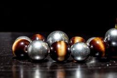 Ound coloriu a colar de pedra na tabela e no fundo pretos Foco seletivo Imagens de Stock Royalty Free
