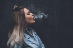 Oung白肤金发的女孩抽电子香烟 免版税库存照片