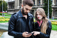Oung adults couple using a mobile phone Stock Photography