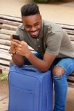 Oung african american man sitting with mobile phone and suitcase Royalty Free Stock Photography