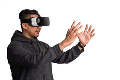 Oung asian man wearing virtual reality goggles holding virtual o. Half profile of young asian man wearing virtual reality goggles holding virtual object, white stock images