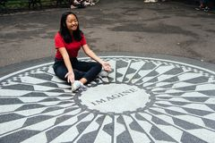 Oung Asian woman sitting on the Imagine mosaic. New York City, USA - June 23, 2018: Young Asian woman sitting on the Imagine mosaic in the Strawberry Fields in royalty free stock images