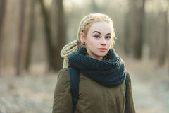 Oung beautiful blonde hipster woman in scarf and parka with dreadlocks hairstyle posing cold season outdoors Royalty Free Stock Photo