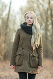 Oung beautiful blonde hipster woman in scarf and parka with dreadlocks hairstyle posing cold season outdoors Stock Photo