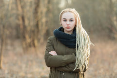Oung beautiful blonde hipster woman in scarf and parka with dreadlocks hairstyle posing with crossed hands cold season outdoors Stock Images