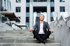 Oung biznesmena obsiadanie na krokach biuro i medytuje obraz royalty free