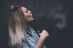 Oung blonde girl smokes electronic cigarette Royalty Free Stock Photo