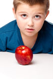 Oung Boy deciding to eat an apple Stock Photography