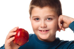 Oung Boy deciding to eat an apple Royalty Free Stock Image