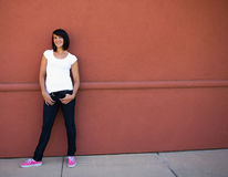 Oung brunette girl red wall hands in pockets Stock Photo