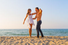 Oung couple teasing one another at the beach Stock Photos
