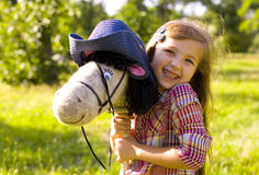 Oung cowboy shirt and a toy horse. Cute little girl with a toy horse fun outdoors Royalty Free Stock Photos