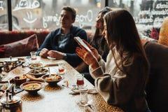 Oung dziewczyna bierze obrazki jedzenie Młoda firma ludzie dymi nargile i komunikuje w orientalnej restauraci L zdjęcie royalty free