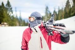 拿着滑雪的Oung人 拿着滑雪的滑雪者看山 英俊的滑雪者人侧视图有面具和拿着的滑雪equipme 库存图片